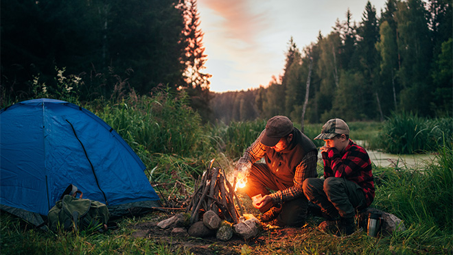 Father And Son Start A Teepee Style Campfire Near Tent