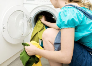 Woman using a front loading washing machine