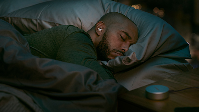 Image of a man sleeping while wearing Bose noise-masking earbuds