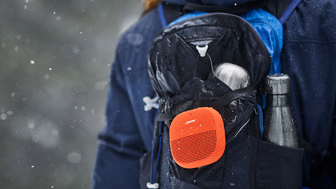 Image of Bose SoundLink Micro speaker on a backpack