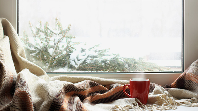 Photo by a window with a cup and blanket