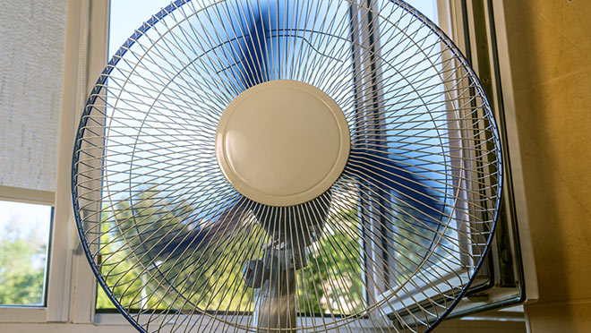 Image of a fan running in front of an open window