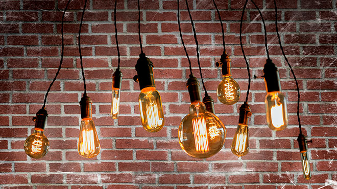 Image of LED filament bulbs against a brick wall