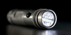 Silver flashlight with a dark background