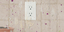 An anthropomorphized wall outlet with oatmeal splatter around it.
