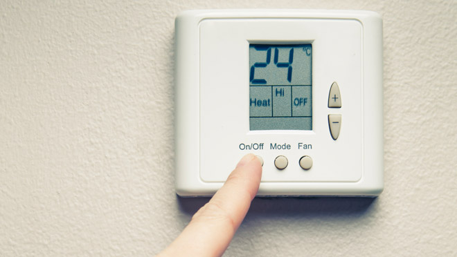 Image of hand with digital thermostat