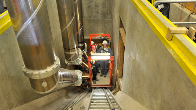 installing conductors in tunnels from the underground units of Mica. A small cart on rails was used to transport works up and down the tunnel.