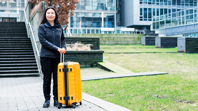Image of Janet Zhu with suitcase