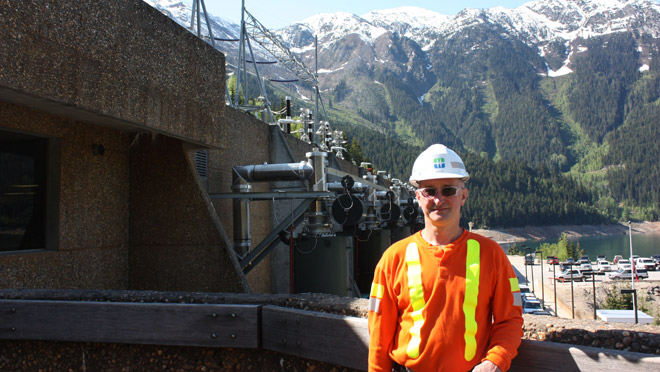 Mica plant manager Morgan McLennan stands atop Mica Dam with 'reactor alley' and Mt. Nagle of the Monashee range in the background.