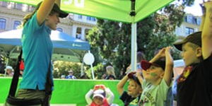 Community outreach representative educating a group of children at an event