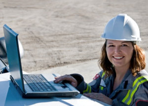 Woman wearing a hardhat working on a laptop at a construction site