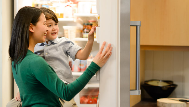 Woman and child looking in a fridge