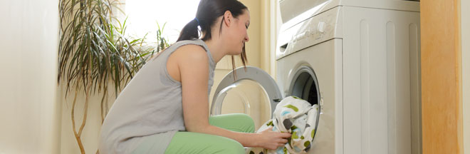 A woman loading laundry machine
