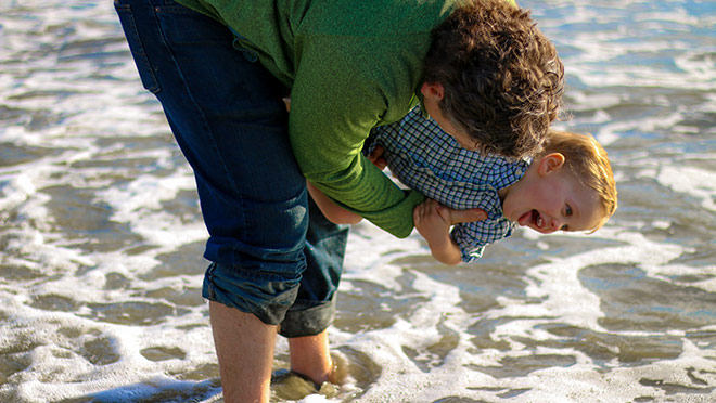 Image of father and son playing at the beach