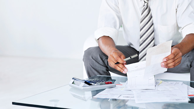 Image of businessman calculating invoices