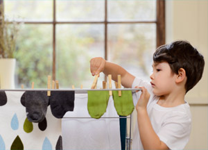 Child hanging clothes to dry