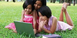 Three children laying on the grass looking at a laptop