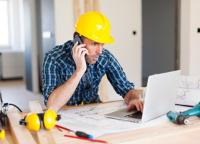 Image of construction worker at laptop, on phone