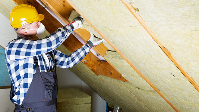 Image of a contractor installing insulation in an attic