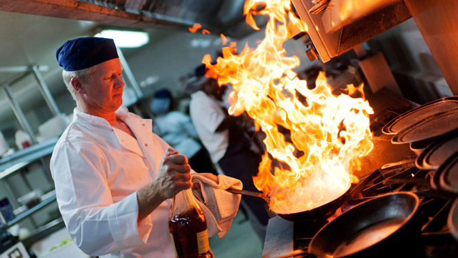 Image of a cook working in a commercial kitchen