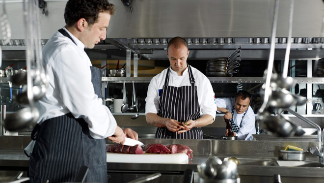 Image of cooks working in a restaurant kitchen