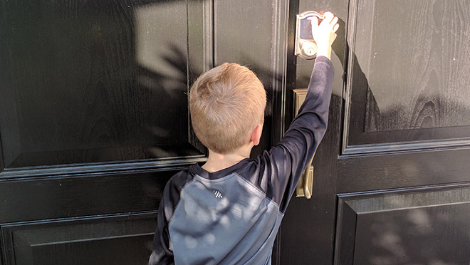 Image of young boy opening door with a Schlage Camelot Wi-fi integrated lock