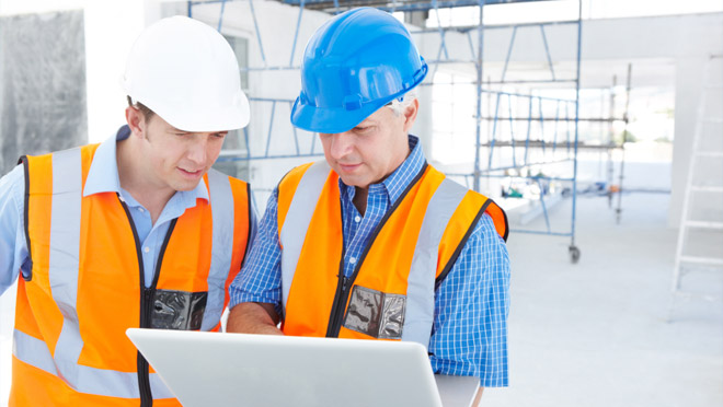 Two workers in safety gear looking at a laptop