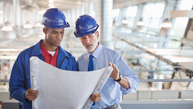 Image of engineers inside a factory looking over drawings
