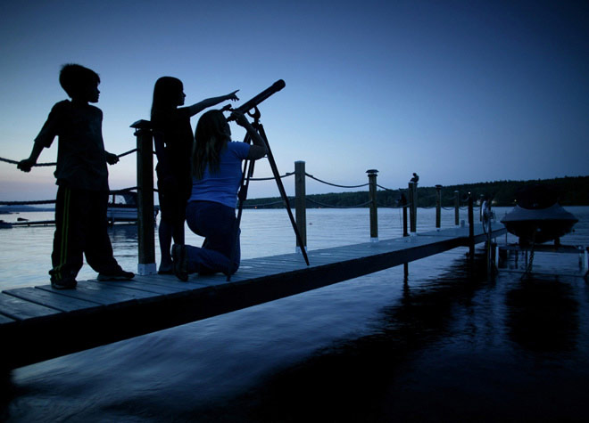 Family looking through a telescope on a dock full width