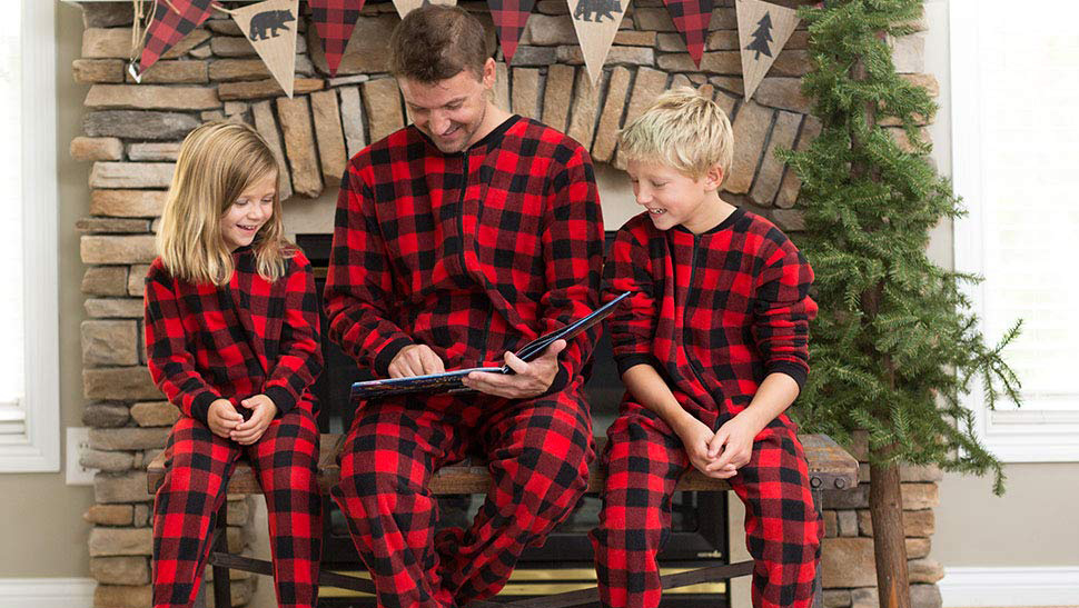 A family reading a book together and wearing matching onesies