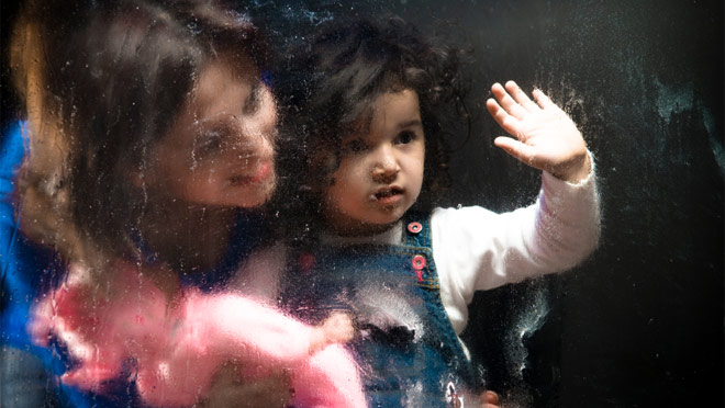 Girl and mother behind glass waving goodbye