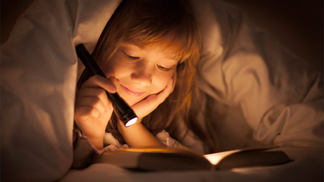 Image of young girl using a flashlight to read a book