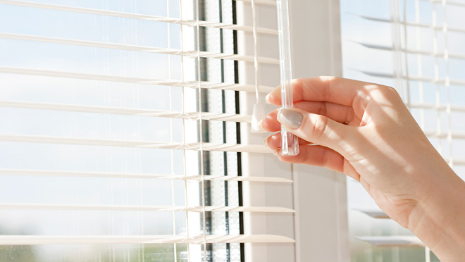 Image of hand closing venetian blinds