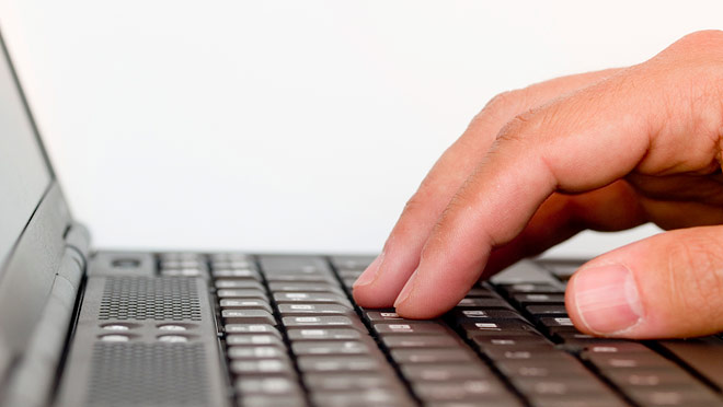 Image of hand using a laptop keyboard