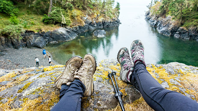 Image of hikers sitting on the edge of a cliff on the B.C. coast