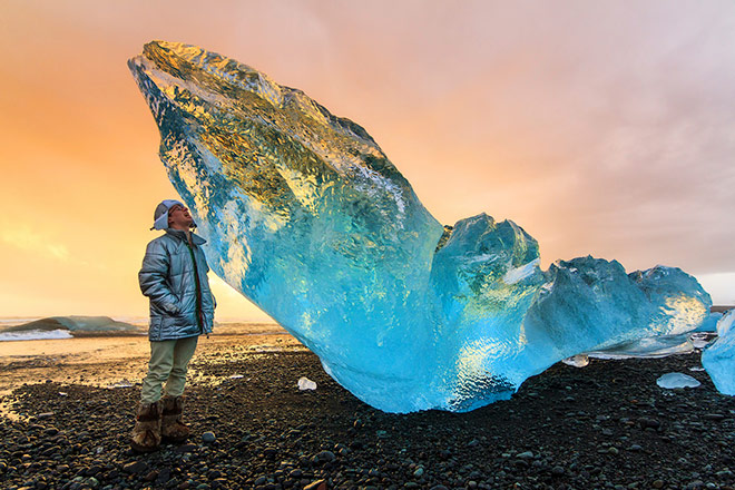 Image of tourist and beached ice chunk in Iceland