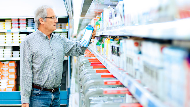 Image of man standing at a supermarket dairy cooler