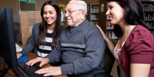 Older man learning to use a computer with two young helpers