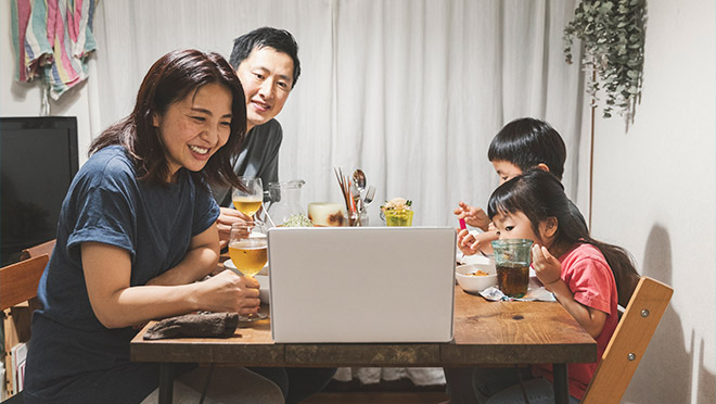 Image of a family eating dinner and meeting remotely