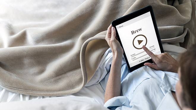 Image of person brewing coffee while using a tablet in bed