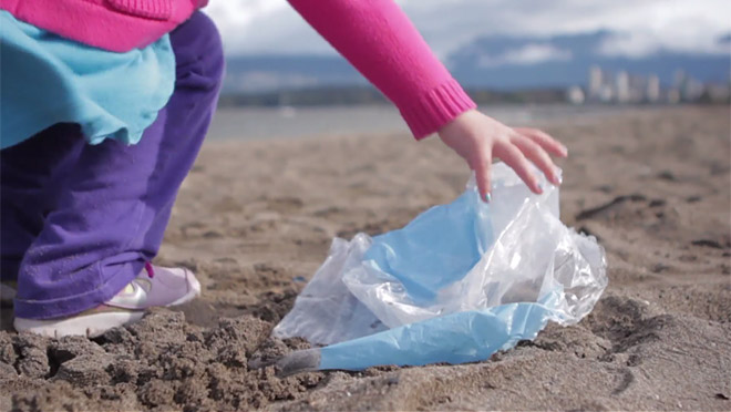 Image of young child picking up trash on a Vancouver beach