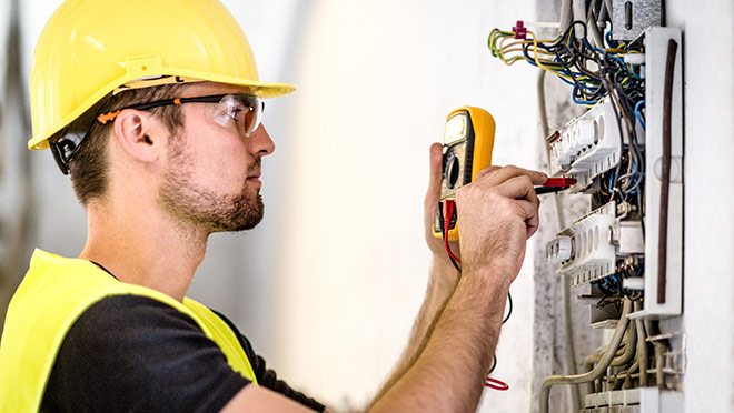 Image of an electrician testing with a multimeter