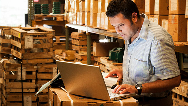 Image of warehouse worker using a laptop computer