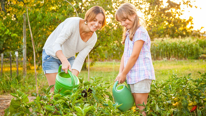 Image of mother and daughter watering plants