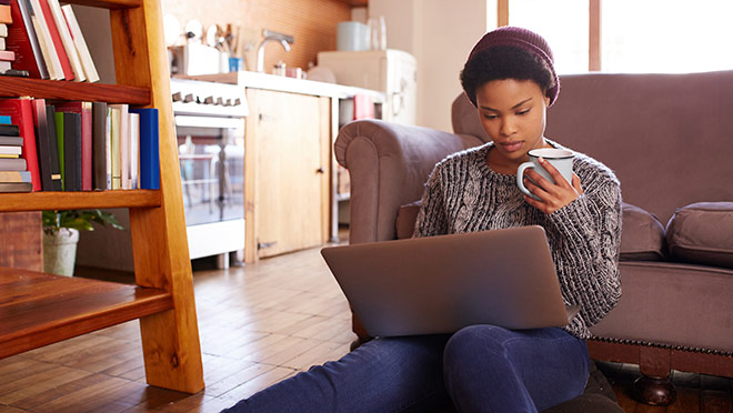 Image of woman drinking coffee and sitting with a laptop