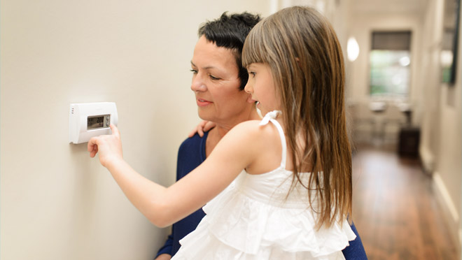 Child with mother turning down a thermostat