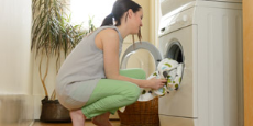 Woman doing laundry using an energy efficient washer dryer