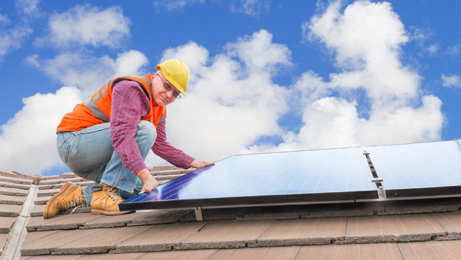 Image of worker installing solar panels