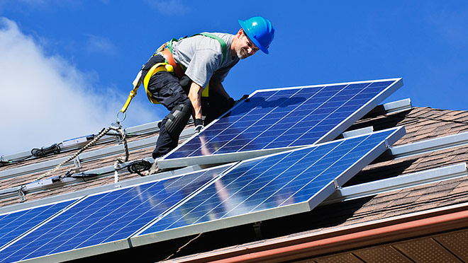 Image of worker installing solar panels on a house roof