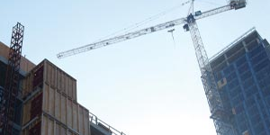 Commercial highrise building under construction with a crane close up